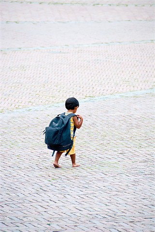 Small boy with heavy load.