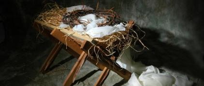 The story of Christmas metaphor represented by a manger and crown of thorns.